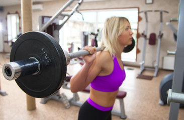 Focused young beautiful girl lifting weights in a gym