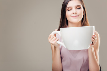 Woman with beautiful manicure holding big white cup of hot coffee.