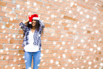 young woman with santa claus hat and snowflakes