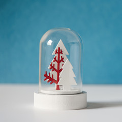 Christmas snow globe with trees, minimalistic scene, blue background, copy space