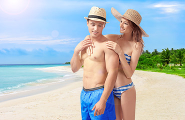 Young couple in swimsuits on white background