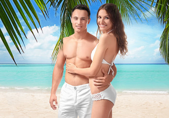 Young couple in beachwear on white background