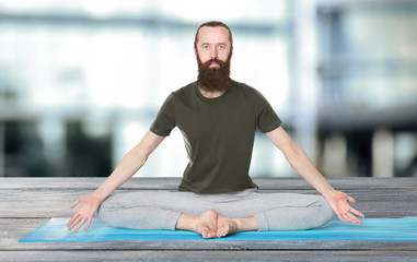 Man practicing yoga on blurred  background