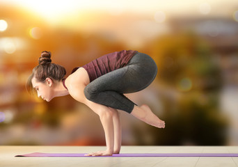 Young woman practicing yoga on light background indoors
