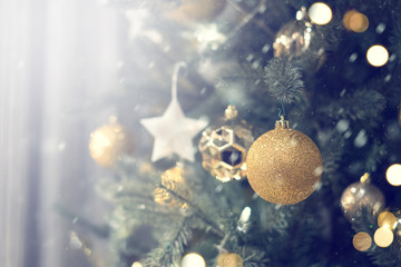 Closeup of gold bauble hanging from a decorated Christmas tree with bokeh, copy space, Xmas holiday background.