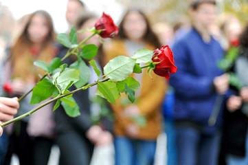 Jugendliche mit roten Rosen bei einer Gedenkfeier