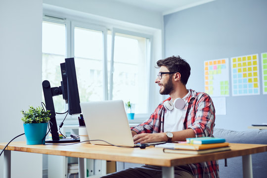 Creative smiling young man working on his start-up business in cozy home office
