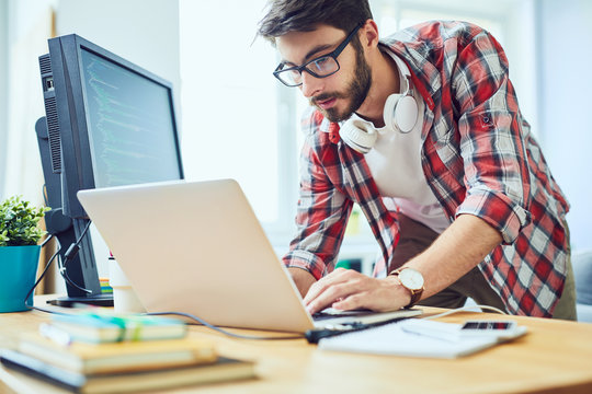Young software developer standing at his desk and working in a hurry