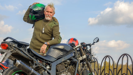 Portrait of a cheerful older man with a motorcycle