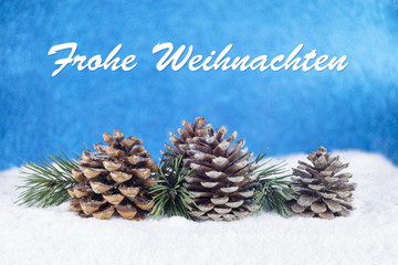 "Group of pine trees and some branches with text in German ""Frohe Weihnachten"" on a white snow and blue background"