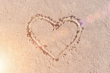 Heart drawn in the sand. Beach background. Top view. Sunny.