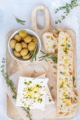 Green olives, feta cheese and fresh ciabata on a wooden board