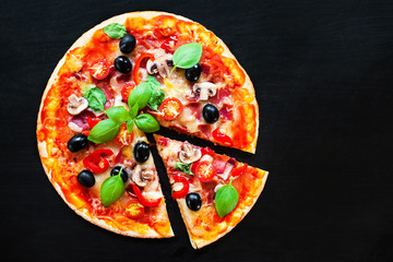 Mozarella Pizza slices with  melting cheese and olives served at a pizzeria or restaurant on black board with copy space