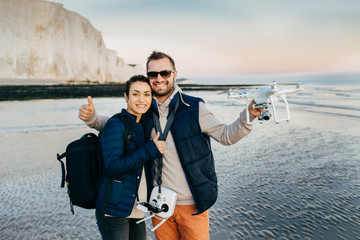 Happy female and male travellers with bags and modern technologies for making photos and video of what they see. Couple in love spend vacations on seaside, try new equipment drone for first time