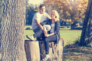 Couple of two young people in love sitting on a wood