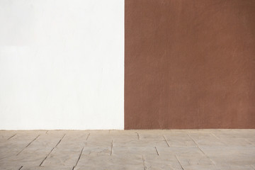 White and brown plastered wall and pavement as background