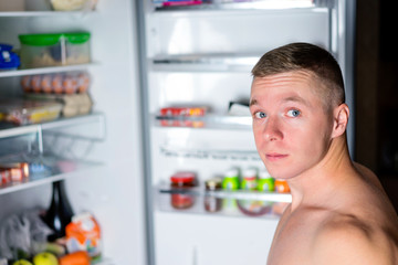man looking for food in the fridge