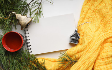 Christmas background with a Cup  of coffee, a notebook, branches of pine with large needles and a yellow sweater. Top view close-up