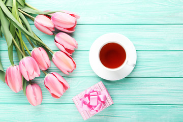 Pink tulips with gift box and cup of tea on wooden table