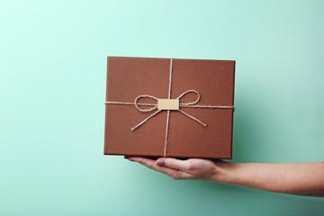 Female hand holding gift box on mint background