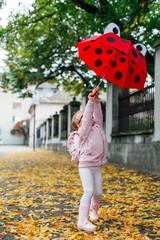 Preschool girl playing on the autumn street