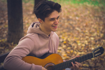 young male guitarist in the park