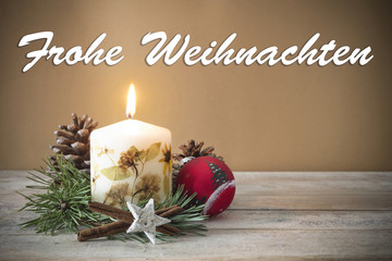 "Christmas decoration with candle, pine, bauble, with text in German ""Frohe Weihnachten"" in wooden background"