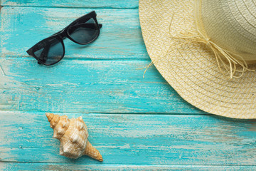 Straw hat, sunglasses and a  seashell on a painted blue paint vintage boards The top view. Close-up