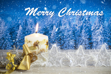 "Christmas decoration with candle, golden bow, silver stars, with text in English ""Merry Christmas"" in a blue forest background"
