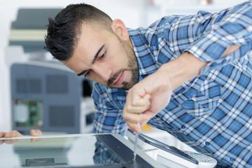closeup shot young male technician repairing digital photocopier machine
