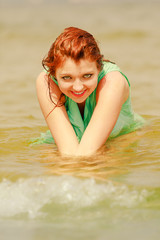 Redhead woman posing in water during summertime