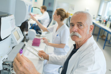 senior doctor examines a medical record in the hospital room