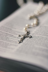 A silver and pearl rosary necklace is placed in the middle of an open page in the bible. The crucifix pendant of the necklace is in focus. The image has great depth of field.