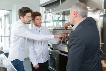 Waiters learning how to use coffee machine