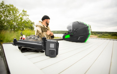 View of sports ation camera with mount with motorcycle helmet and man on the background.