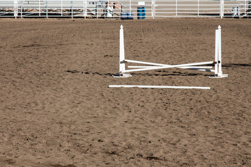 Single white horse jumping ring at a county fairgrounds with fallen rail