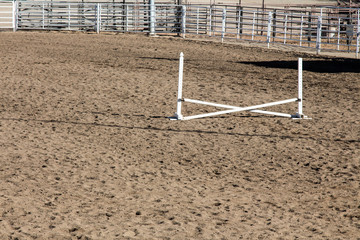 Single white horse jumping ring at a county fairgrounds