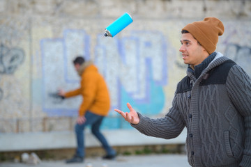 graffiti artist playing with spraying can