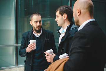 Colleagues in a discussion about business on a coffee break in front of office