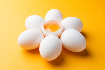 White eggs and egg yolk on the yellow background