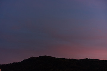 sunset with violet sky and mountain with tv tower