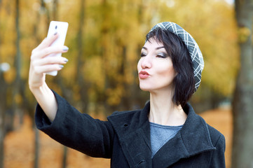girl photographs herself on the phone and kisses in autumn city park, yellow leaves and trees, fall season