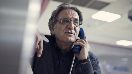 Senior man talking on public payphone