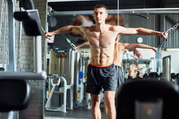 Front view portrait of handsome muscular man with no shirt using exercising machines in modern gym standing against mirror