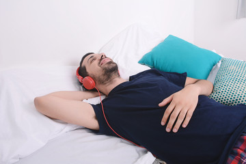 Man listening to music in bed.