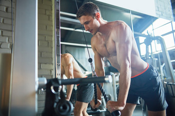 Portrait of handsome muscular man with bare chest training in gym using exercising machines, copy space