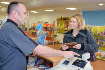 smiling young male store clerk serving purchaser at cash desk