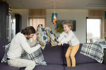 Pillow fight between father and little son in living room, happy dad and child boy playing on sofa fighting with cushions, daddy laughing having fun with his kid together, leisure activity at home