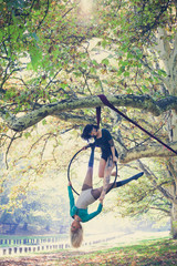 two young women aerial hoop  dance in forest