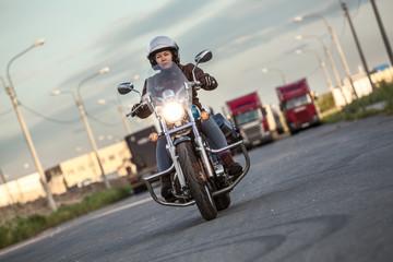 Woman motorcyclist riding on chopper with turning on headlight on asphalt urban road